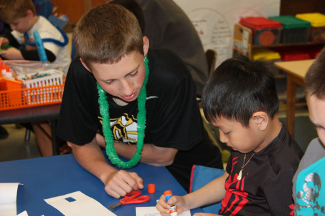 John Pybas helps a young student at Bierbaum Elementary in Mrs. Buckley