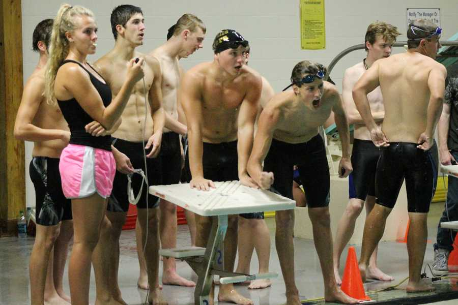 Jarad Wahl (11) and Chad Elking (11) cheer on their teammates at their meet on Sept. 5 against CBC and Washington.