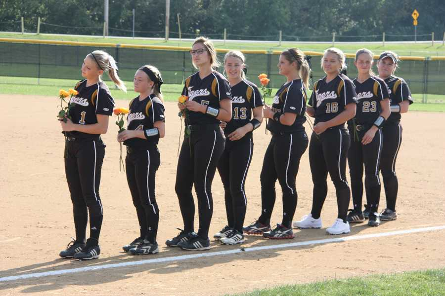The+senior+softball+players+stand+on+the+first+base+side+as+they+wait+to+meet+their+parents.+The+seniors+were+honored+at+their+home+game+against+Fox+on+Thursday%2C+Sept.+18.+They+beat+the+Warriors+7-1.