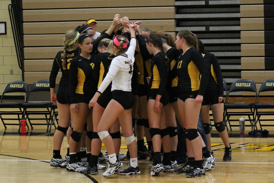The varsity volleyball team stands in a huddle during their game on Friday, Aug. 22. The team played Francis Howell for their first home game.
