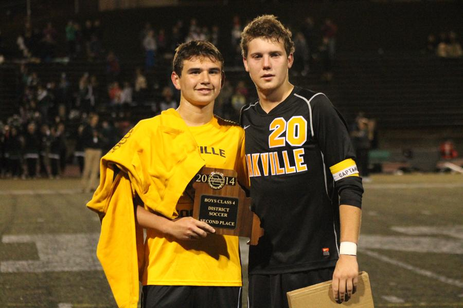 Thomas Hutcheson (12)(left) and Justin Pike (12) stand with the district tournament runner-up plaque. OHS lost to Mehlville in the district championship game on Oct. 30; the final score was 3-1.