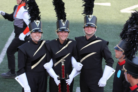 Drum majors Madison Stinnett (12) (left), Erin Elking (12), and John Hall (12) stand with the trophy they received in Oklahoma for their performance in the band competition.