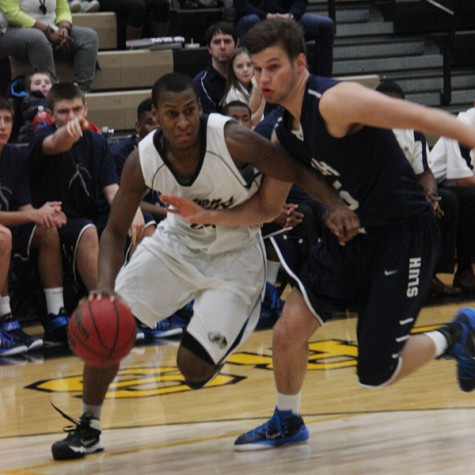 Joe Green (12) dribbles past a St. Louis University High defender. Green was OHS's third-highest scorer with 11 points on the game.
