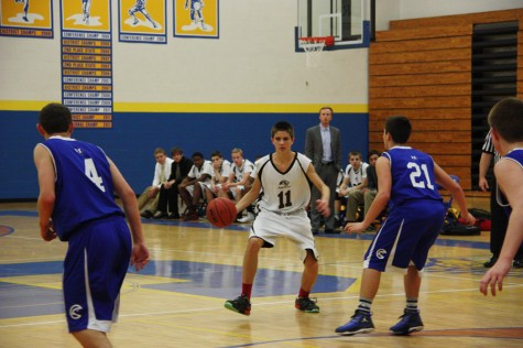 Tom Hoffmeister (9) dribbles towards the hoop in the freshman basketball team
