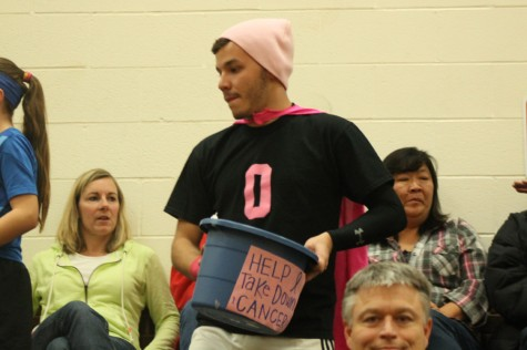 Eric Tate (12) collects money at the annual Pink Out basketball game.