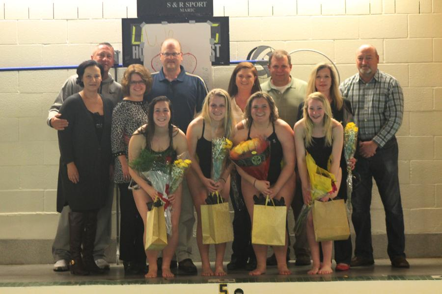 The four senior girls take a picture with their parents as they hold their bags and certificates.