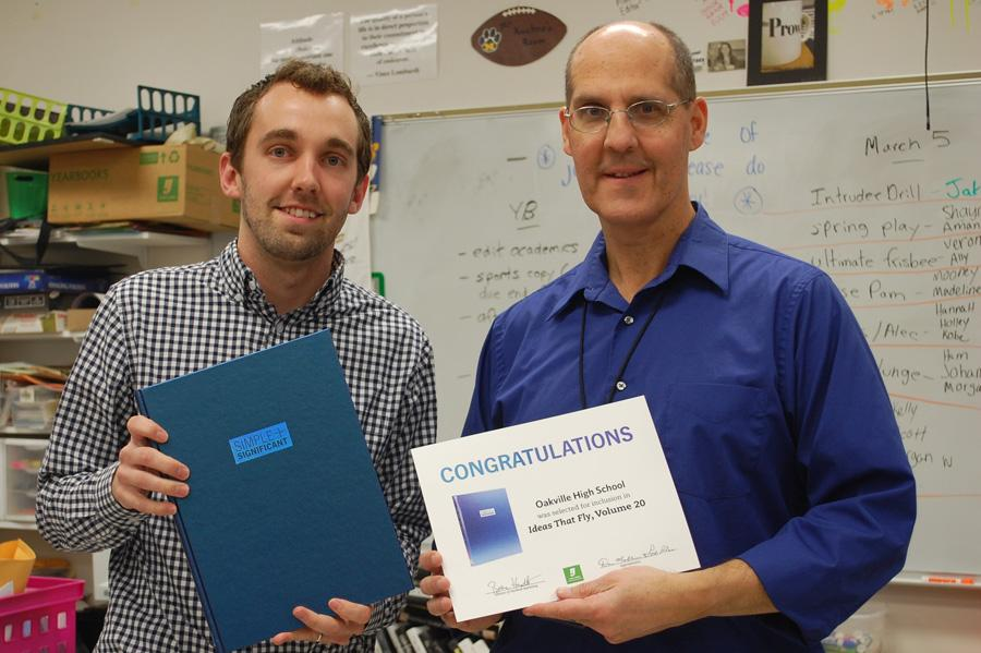 Yearbook advisor Jeff Kuchno (right) stands with Dan Mueller (left), the Herff Jones representative, as he presents the award.