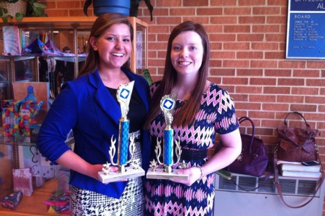 Madison Stinnett (left) poses with Brittany Cox (right) as they hold up their district trophies.