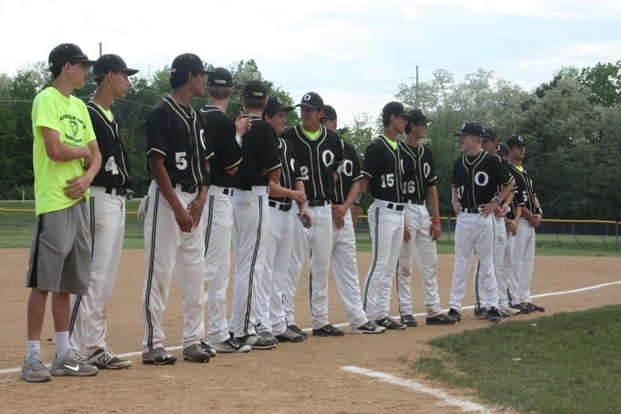 The sophomores and juniors on the OHS varsity baseball team stand while the team's 12 seniors are honored before the  Tigers' game against Lindbergh on May 5.