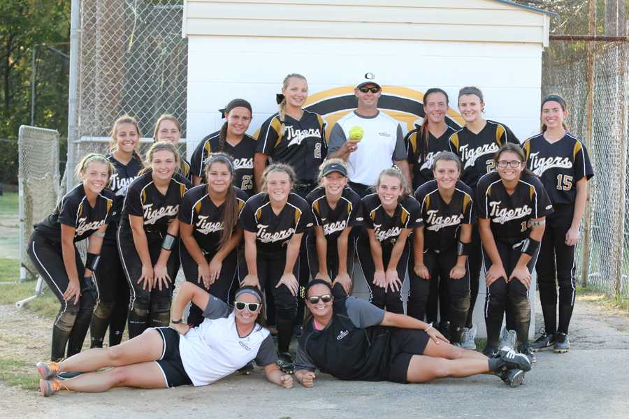 The softball team gets a picture with Coach Sturm after the game.