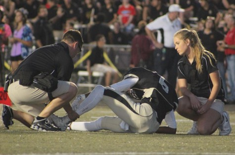 Athletic trainer Mike Atkinson helps wide receiver Antwan Banks (12) after he got injured in the first quarter. Banks did not play the rest of the game.