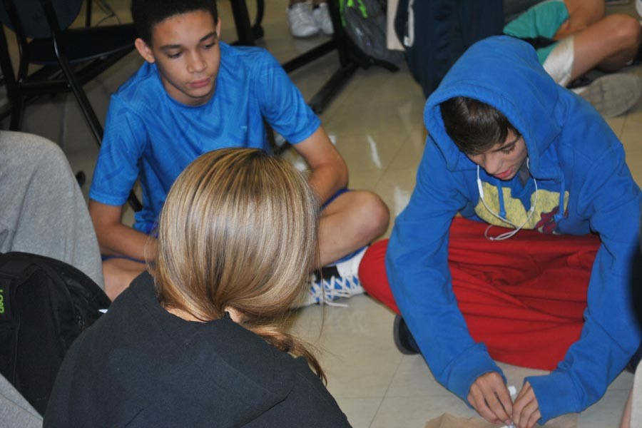 A leadership mentor watches two freshman participate in the toothpaste activity.