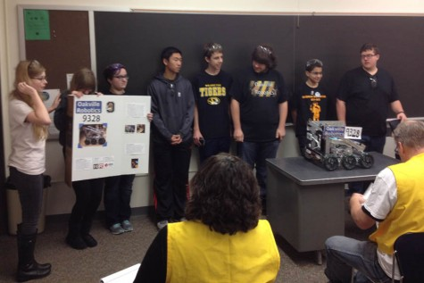 The robotics team stands with their robot.