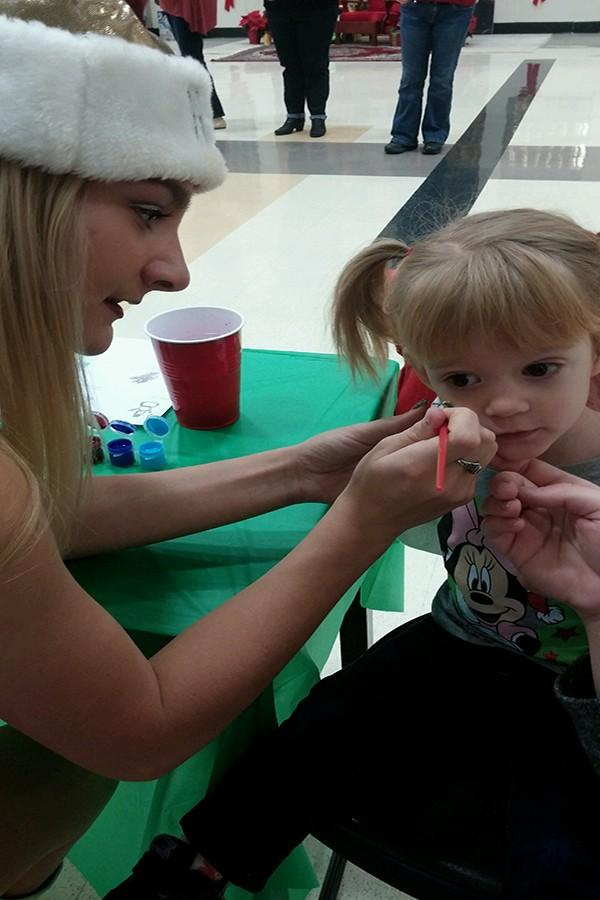 A Golden Girl paints a child's face at the second annual Breakfast with Santa.