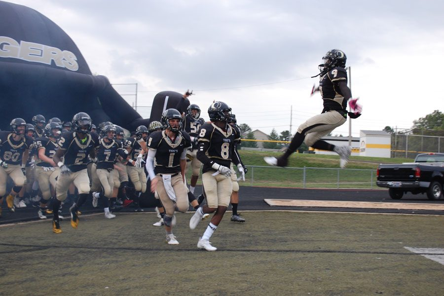 The+varsity+football+team+emerge+from+their+new+entrance+for+the+first+home+game.+Demetrius+Harris+%2812%29+and+Jevon+Jones+%2812%29+lead+the+team+on+to+the+field.++