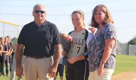 Emily Davidson (12) stands with her parents on Senior Night on Sept. 22.
