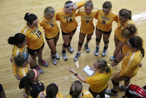 The varsity girls volleyball team huddles up to discuss strategies before game.