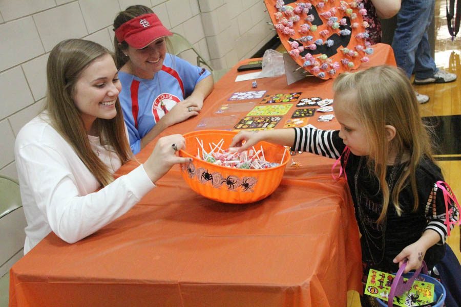 During Trick or Treat Tuesday on Oct. 25, Danielle Arconati (12) and Emily Davidson (12) pass out candy to little girl.