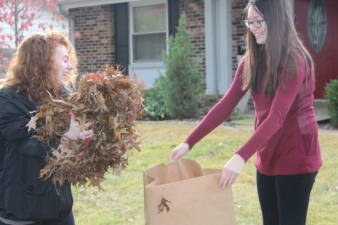 Holding open a lawn bag, Dalia Dzekic (11) helps her friend Katelyn Henry (11) collect leaves during OHS