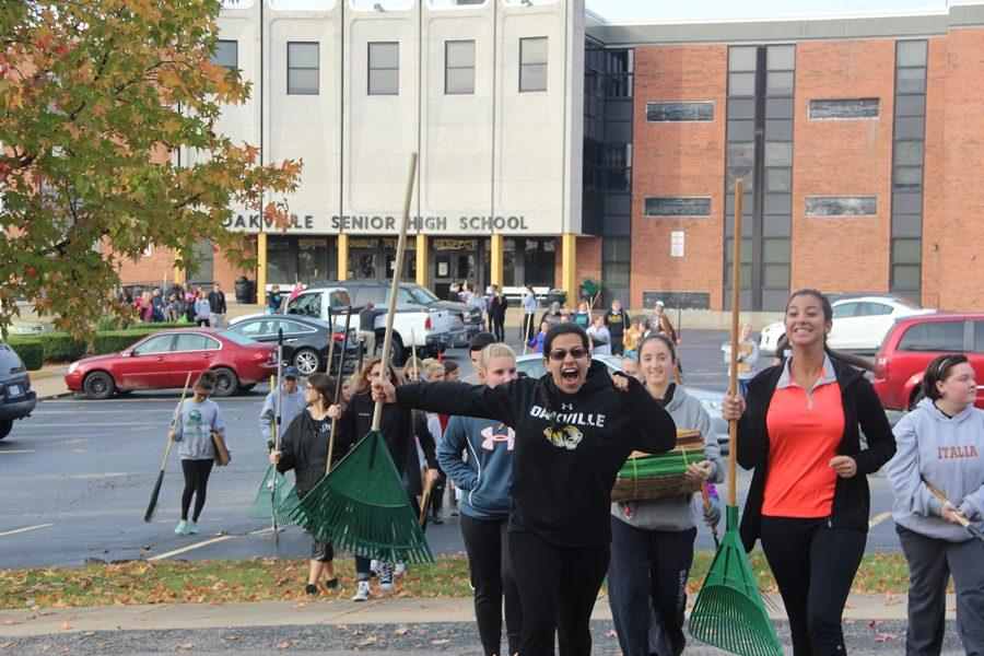 Getting ready for the annual Rake 'n Run, Hiba Al-Ramahi (12) runs across the street with Simone Hanna (12). Al-Ramahi was raking with National Honor Society (NHS) and Student Council.