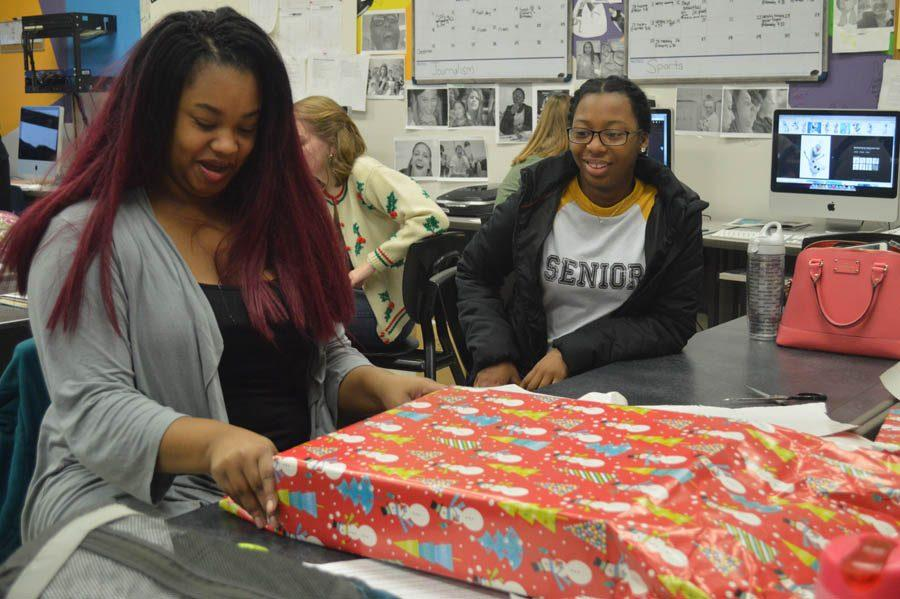 Students help wrap gifts for the Community Care Project.