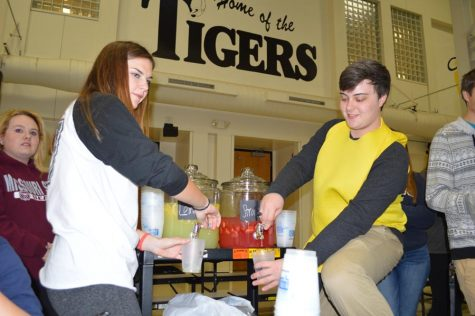 Pouring lemonade, Victoria Ratcliff (12) and Matt Argent (12) help run their lemonade stand making $60 in profit.