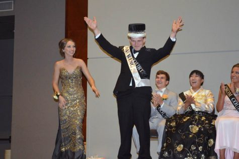 Raising his arms in celebration, Prom King Austin Hallet (12) acknowledges the crowd.