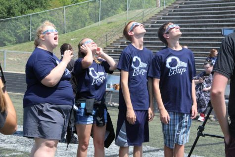 Wearing their eclipse shirts, a group of students looks up mesmerized by the eclipse.