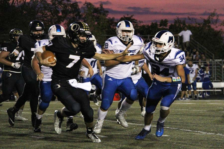 Quarterback Jordan Jost (12) carries the ball at the Sept. 8 homecoming game. OHS won 17-7.
