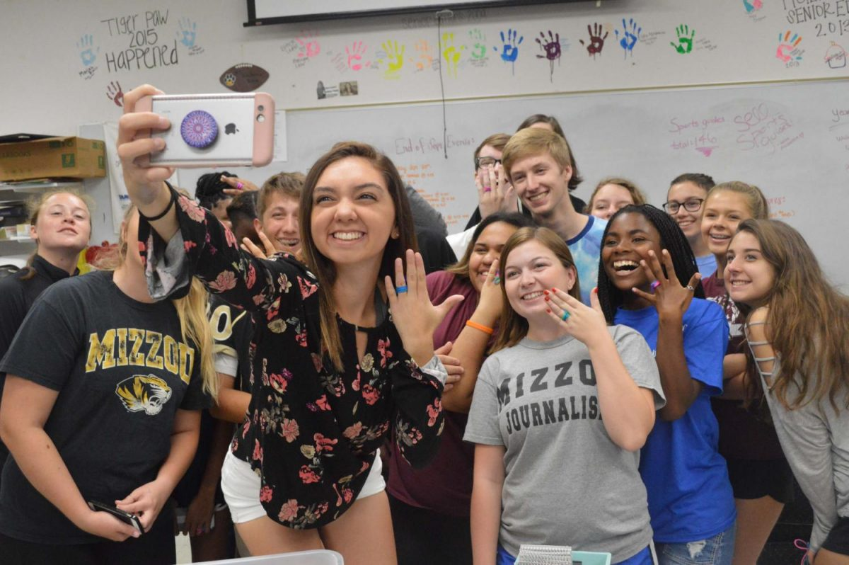 Taking a group selfie with a big smile on her face,  Rachel Delgado (12) shows off her new wedding ring with the rest of the yearbook staff.