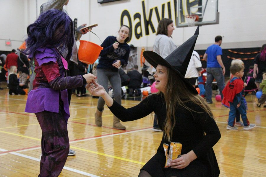 Dressed as a witch, Ally Turner (10) hands candy to a child in costume at Trick or Treat Tuesday on Oct. 24.
