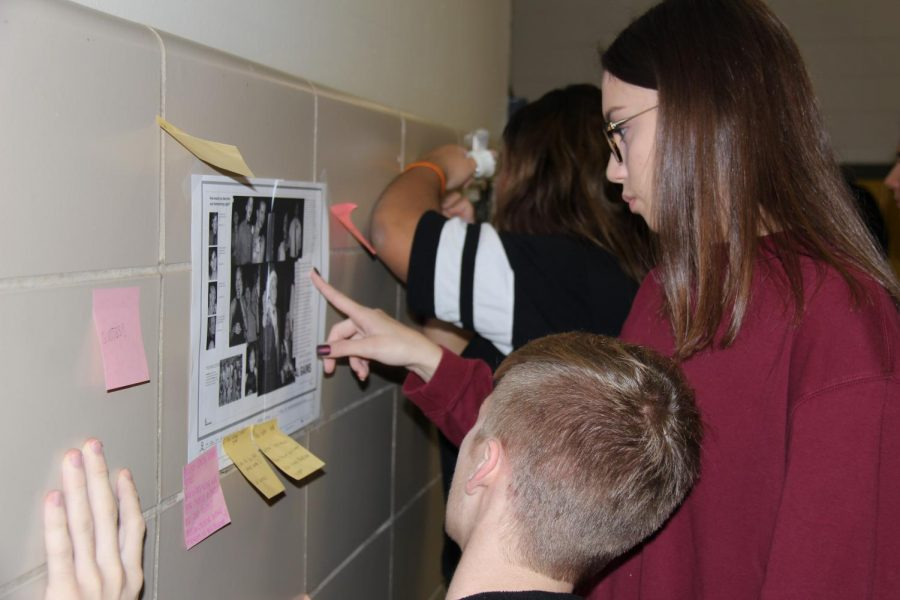 Analyzing a yearbook spread on the wall, Kayleigh Tritschler (11) and David Cormack (11) point out the flaws on the page.