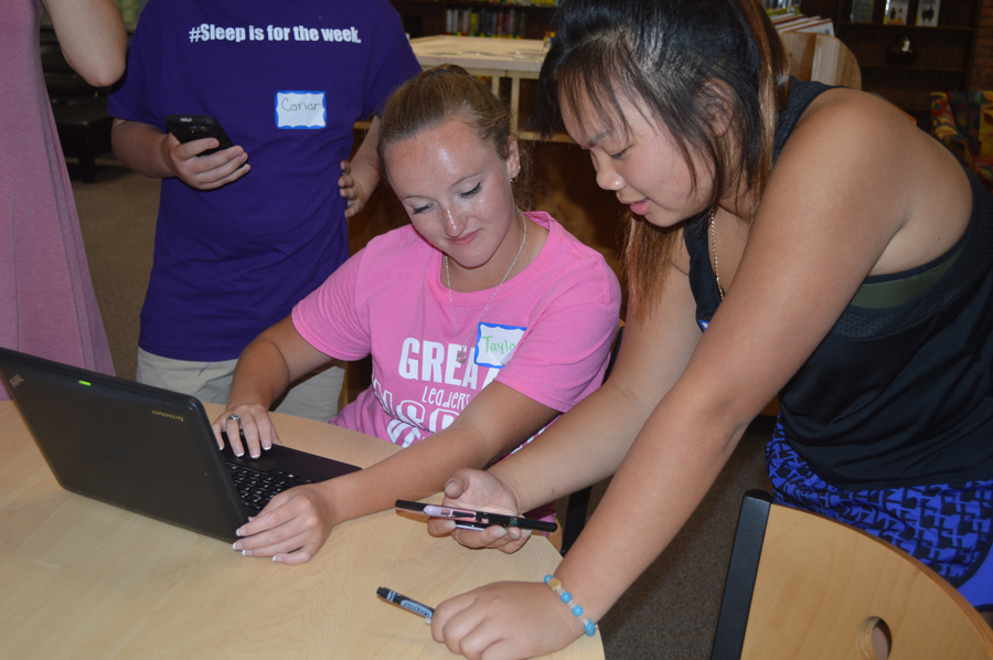 Student body president Taylor Zapf (12) checks out the new app with STUCO member at STUCO meeting on Sept. 21.