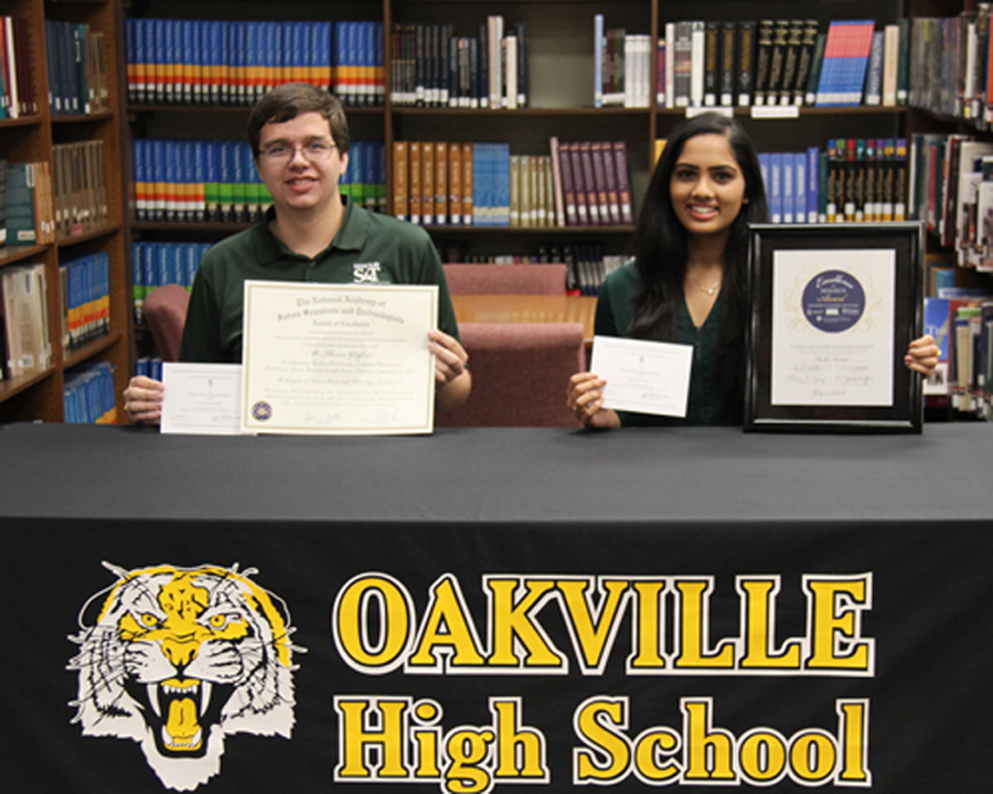 Thomas Gleiforst (12) and Preethi Tumati (12) pose with their certificates in the library on Sept. 29.