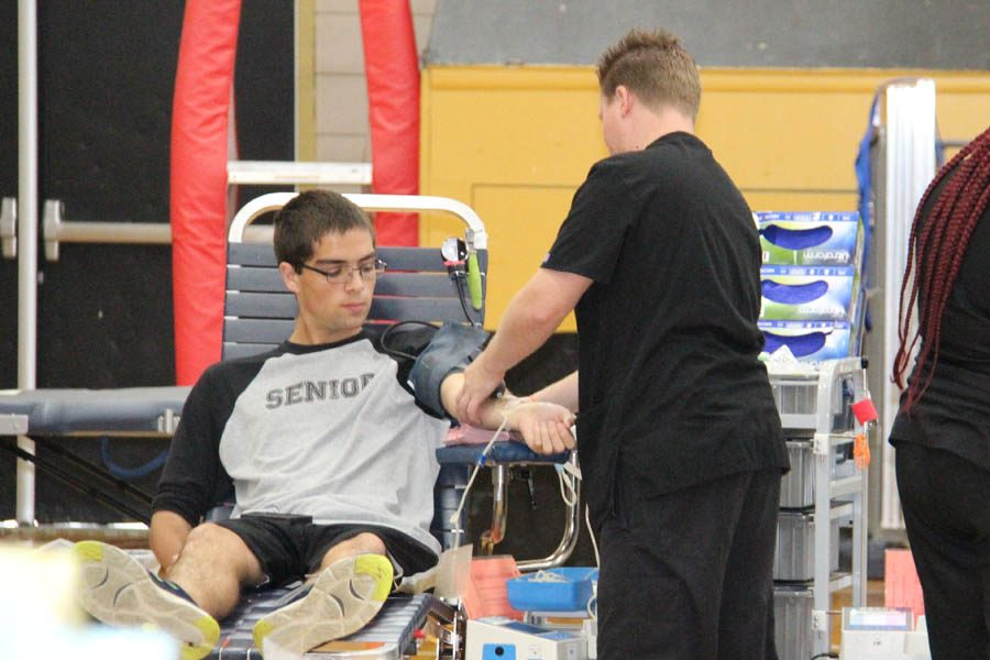 Staring down at his arm, Greg Davidson (12) watches the nurse draw his blood at the blood drive on Oct. 27.