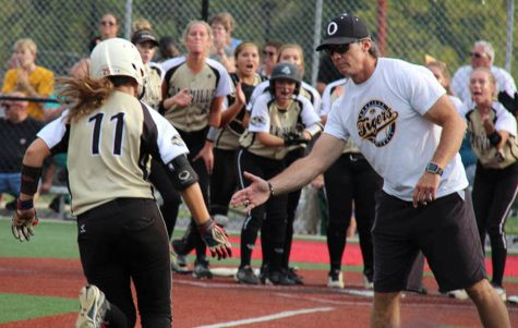Rounding thirdafter a home run, Maddie Michalski (12) accepts congratulations from Head Coach Rich Sturm as the rest of the team awaits her at the plate during the Oct. 6 district championship game at Fox.