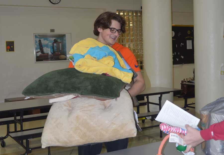 Justin McCrady (11) collects dog beds during the 2016 Presents for Paws.