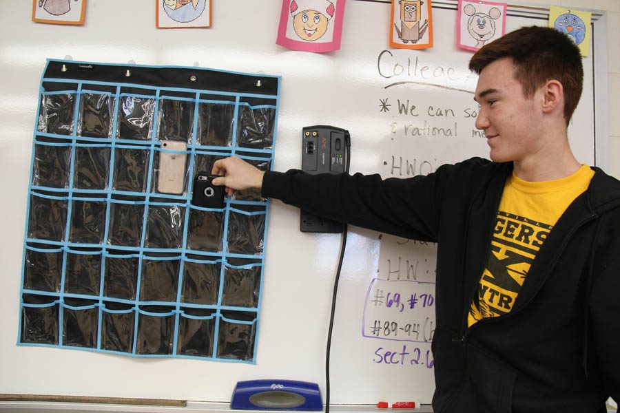 Mark Pinner (12) places his phone in Ms. Quesenberry's shoe hanger on Nov. 10.