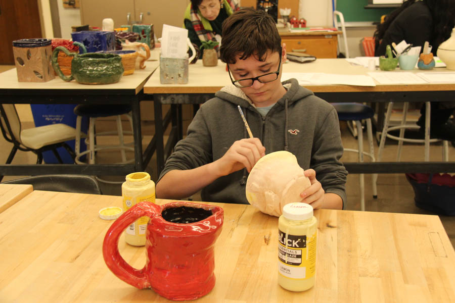 Ceramic I student Sanin Velijevic (11) glazes his final project during 6th block on Dec. 13.