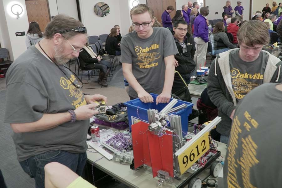 Dr. Jim Kreyling, Jacob Walters (10), and Caleb Roth (12) put the finishing touches on team 9612's robot before taking it into competition.