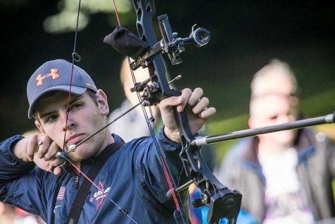 Steven Collins (12) pulls back his arrow and focuses on his target.