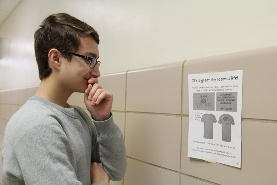 French student analyzes flyer on the wall outside Room 235 on March 2.