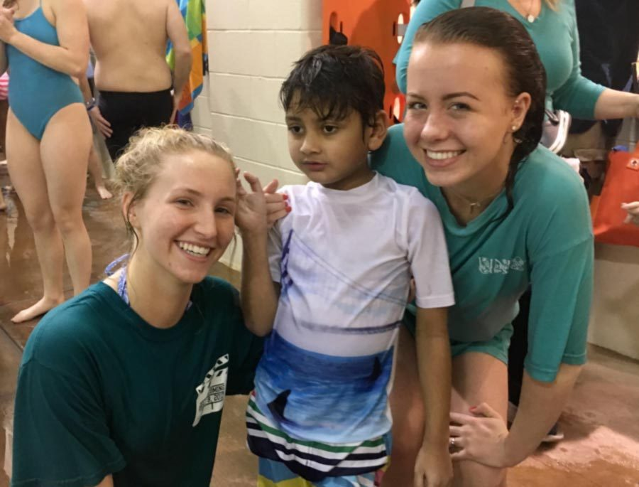 Maddy McClure (12) and Caitlyn Kelly (12) pose with their buddy after a KEEN swim on Jan. 28.