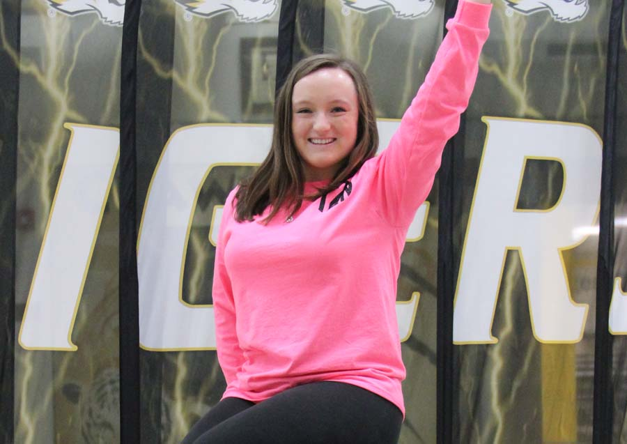 Taylor Zapf (12) poses on top of the tiger statue in the commons.
