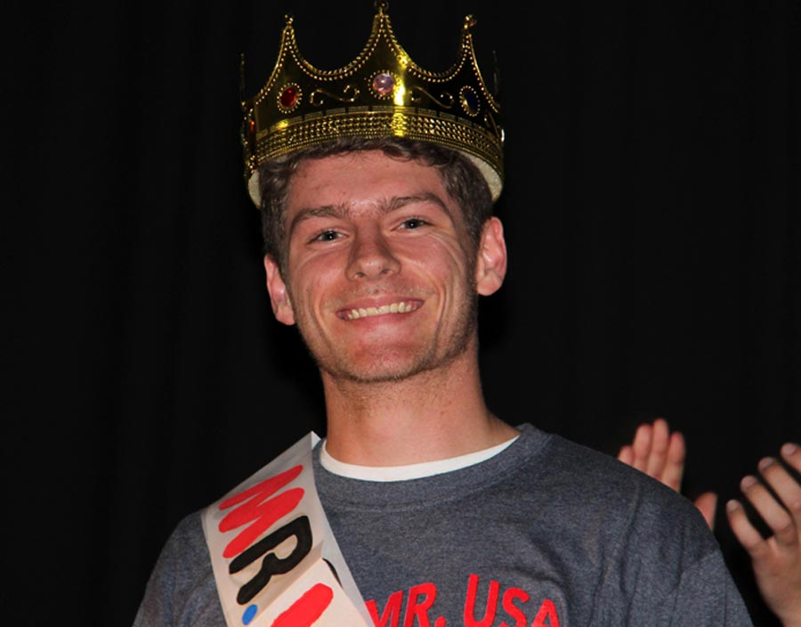 Mr. DECA Brad Hartmann (12) smiles with his crown.