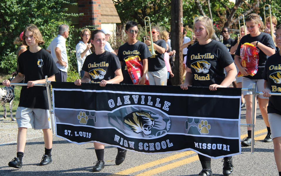 Marching Band members hold banner while marching in the 2017 Homecoming parade.