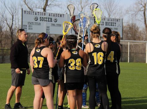 The girls lacrosse team huddles before a game.