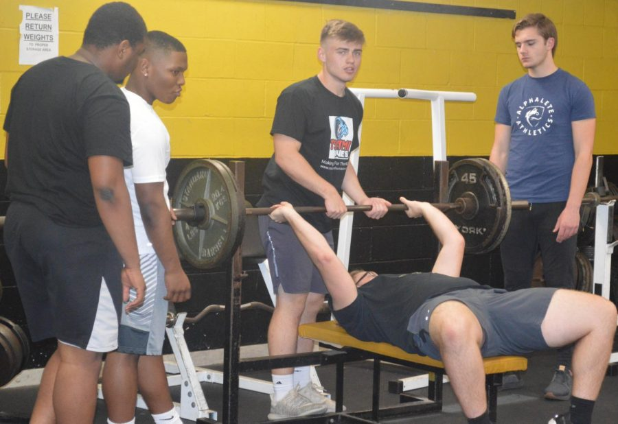 Players of the football team lift weights as part of their new intensive workouts.