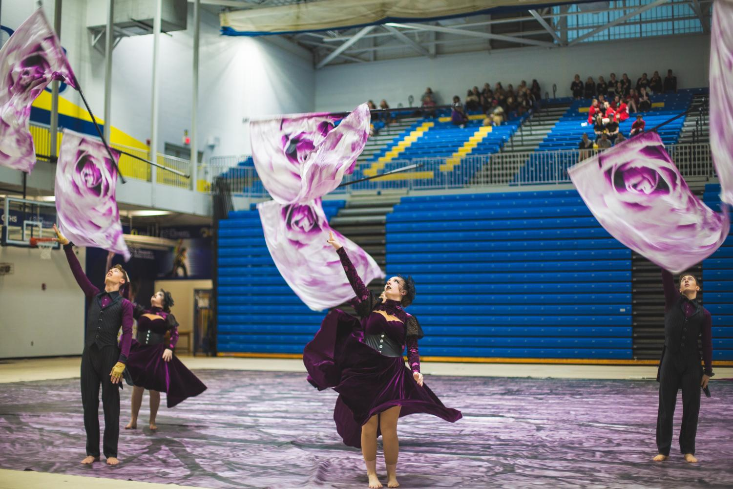 Ben Lanier (10), Jenna Yeager (10), and Caden McGivlery (9) perform at the O'Fallon Township winter guard competition.