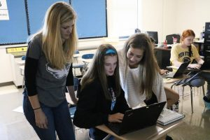 Mrs.Beck helps Brooke Seyer and Grace Bayer with Chromebook in her government class